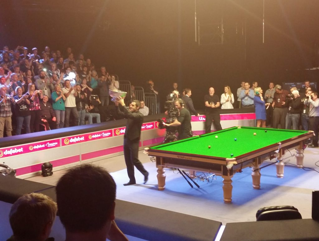 Picture of Ronnie OSullivan flashing his Champion of Champions trophy 2014 to the crowd