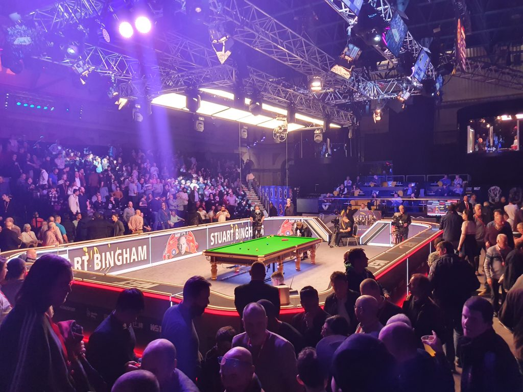 Photo of the snooker arena at Alexandra Palace with a snooker table in the middle an spectators around it