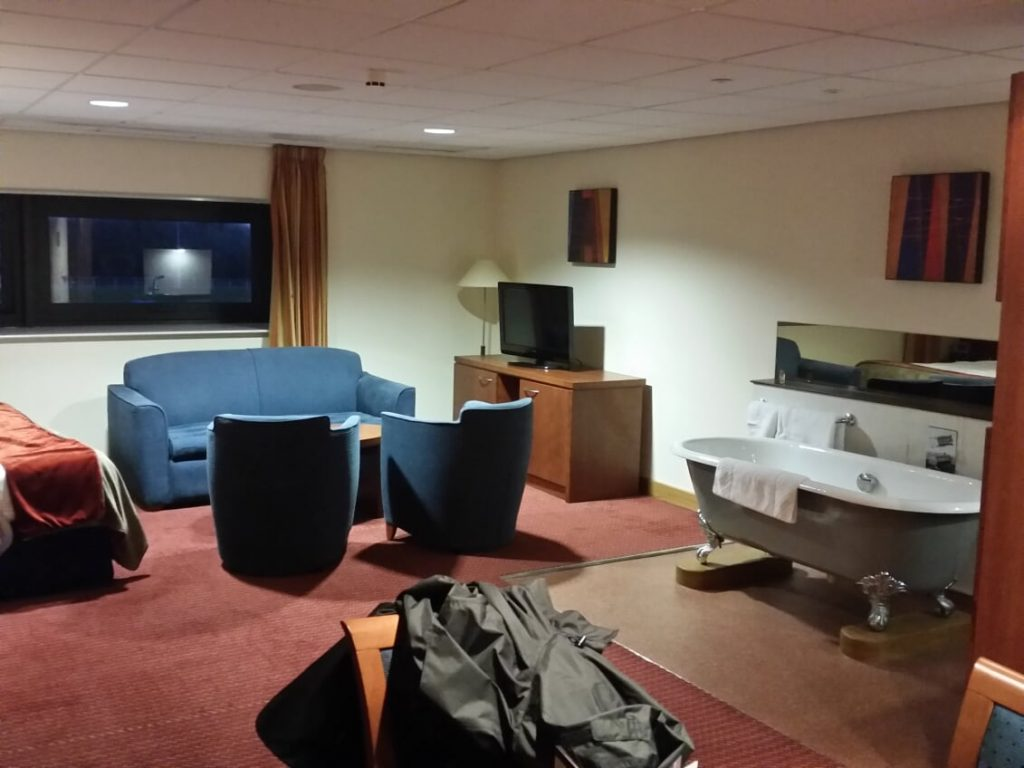Image of hotel room at Ricoh Arena with a free-standing bath tub to the right and a blue sofa to the left